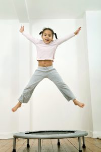 girl child playing on a trampoline