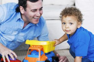 man with his little kid playing with a toy dumper truck